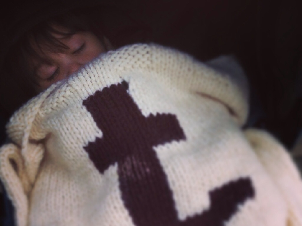 Baby sleeping under knitted blanket with a T